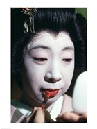 Close-up of a geisha applying lipstick to her lips
