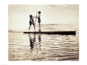 Two boys standing on a wooden platform in a lake