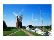 Boat moored near a traditional windmill, River Ant, Norfolk Broads, Norfolk, England