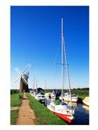 Boats moored near a traditional windmill, Horsey Windpump, Horsey, Norfolk Broads, Norfolk, England