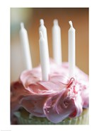 Close-up of a pink frosted cupcake with white unlit candles