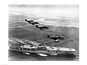 High angle view of four fighter planes flying over an aircraft carrier, US Navy Banshees, USS Coral Sea (CV-43)