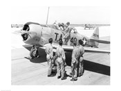 Rear view of four soldiers standing near a fighter plane, T-6 Texan