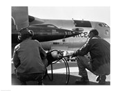 Rear view of two men crouching near fighter planes, X-15 Rocket Research Airplane, B-52 Mothership
