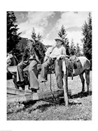 Teenage cowboys sitting on rail fence