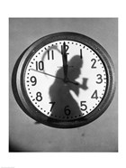 Close-up of the shadow of a person carrying a scythe on a clock