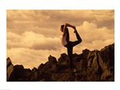 Silhouette of a young woman Practicing Yoga on Mountainside