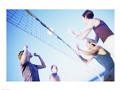 Low angle view of two young couples playing beach volleyball