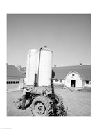 USA, Farmer Working on Tractor, Agricultural Buildings in the Background