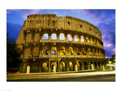 Low angle view of the old ruins of an amphitheater lit up at dusk, Colosseum, Rome, Italy