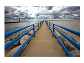 Pier with blue railings jutting out to ocean with red lighthouse in background