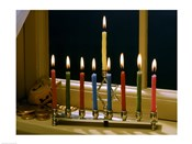 Close-up of a menorah with burning candles and a Star of David