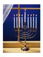 Close-up of burning candles on a menorah at a window