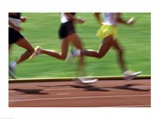 Low section view of male athletes running on a running track