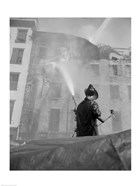 Firefighter pouring water on burning building, low angle view
