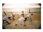 Group of people performing yoga on the beach