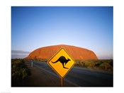 Kangaroo sign on a road with a rock formation in the background, Ayers Rock