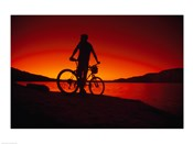 Silhouette of a man standing with his mountain bike, Lake Powell, Utah, USA