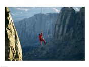 Rear view of a man rappelling down a rock