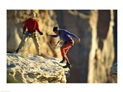Two hikers with ropes at the edge of a cliff