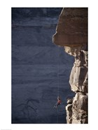 Man hanging from a rope on the edge of a cliff