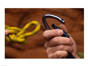 Close-up of human hands holding a carabiner and rope