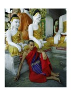 Monk Sitting in Front of a Buddha Statue