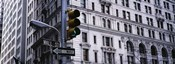 Low angle view of a Green traffic light in front of a building, Wall Street, New York City