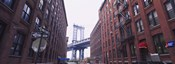 Low angle view of a suspension bridge viewed through buildings, Manhattan Bridge, Brooklyn, New York City, New York State, USA