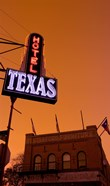 Low angle view of a neon sign of a hotel lit up at dusk, Fort Worth Stockyards, Fort Worth, Texas, USA