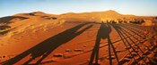 Shadows of camel riders in the desert at sunset, Sahara Desert, Morocco