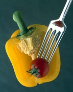 Close up of half yellow pepper with cherry tomato in center on fork tines