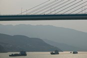 Container ships passing a newly constructed bridge on the Yangtze River, Wanzhou, Chongqing Province, China