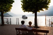 Couple sitting on bench and watching ferry approaching dock along the Lake Como, Bellagio, Province of Como, Lombardy, Italy