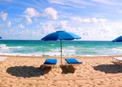 Lounge chairs and beach umbrella on the beach, Fort Lauderdale Beach, Florida, USA