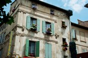 View of an old building with flower pots on each window, Rue Des Arenes, Arles, Provence-Alpes-Cote d'Azur, France