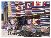 Two female vendors dressed in Mayan costumes displaying products