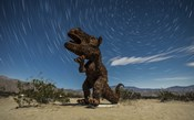 Tyrannosaurus rex sculpture against a backdrop of star trails, California