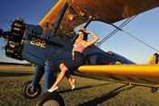 1940's style pin-up girl sitting on the wing of a Stearman biplane