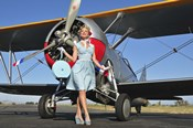 Elegant 1940's style pin-up girl standing in front of an F3F biplane