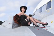 Glamorous woman in 1940's style attire sitting on a vintage aircraft