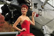 Redhead pin-up girl in 1940's style dancer attire holding on to a vintage aircraft propeller