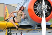 1940's style pin-up girl posing on a T-6 aircraft