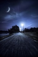 A road in a park at night against moon and moody sky, Moscow, Russia