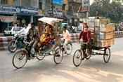 People and cargo move through streets via rickshaw, Varanasi, India