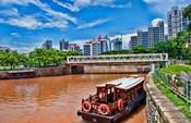 Singapore skyline and tug boats on river.