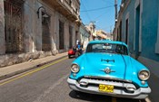 Cuba, Camaquey, Oldsmobile car and buildings