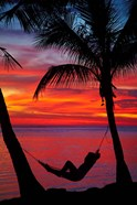 Woman in hammock, and palm trees at sunset, Fiji