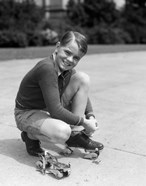 1930s Smiling Boy Fastening On Metal Roller Skates