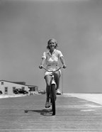 1940s Summer Time Smiling Woman Riding Bike On Beach Boardwalk